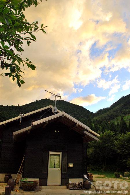 黄色く染まった雲と山小屋
